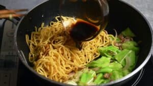 pouring the sauce over the yakisoba noodles