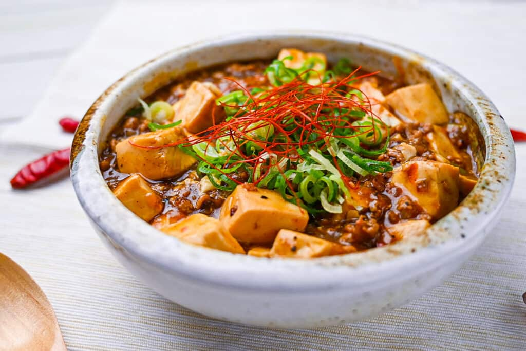 Mabo tofu topped with spring onion and chili threads side view