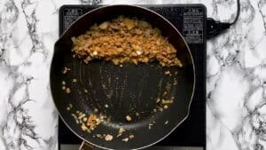 Pushing cooked meat to the side of a pan