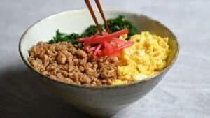 Sanshokudon steps: Garnishing with red pickled ginger