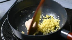 Frying finely diced garlic and ginger in a pan with beef fat
