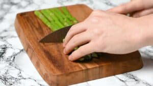Cutting asparagus into thirds on a wooden chopping board