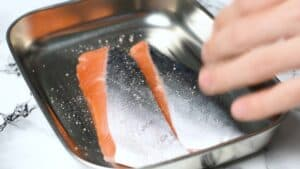 Sprinkling two fresh salmon fillets with salt