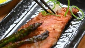 eating miso glazed salmon with chopsticks