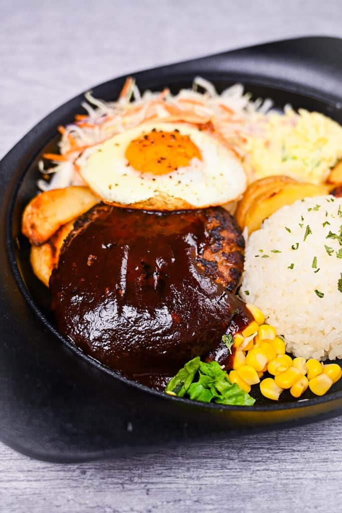 Japanese hamburg steak coated in sauce and served with rice, wedges, corn, salad and a fried egg