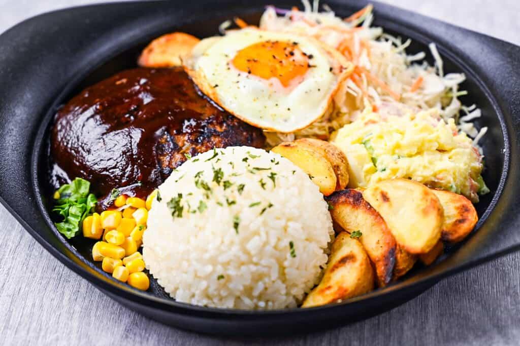 Japanese hamburg steak with rice, wedges, corn, salad, potato salad and egg