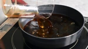 pouring soy sauce into a pan