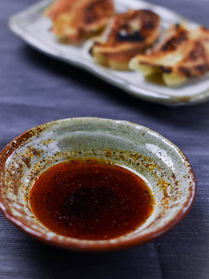 Gyoza dipping sauce with gyoza in the background