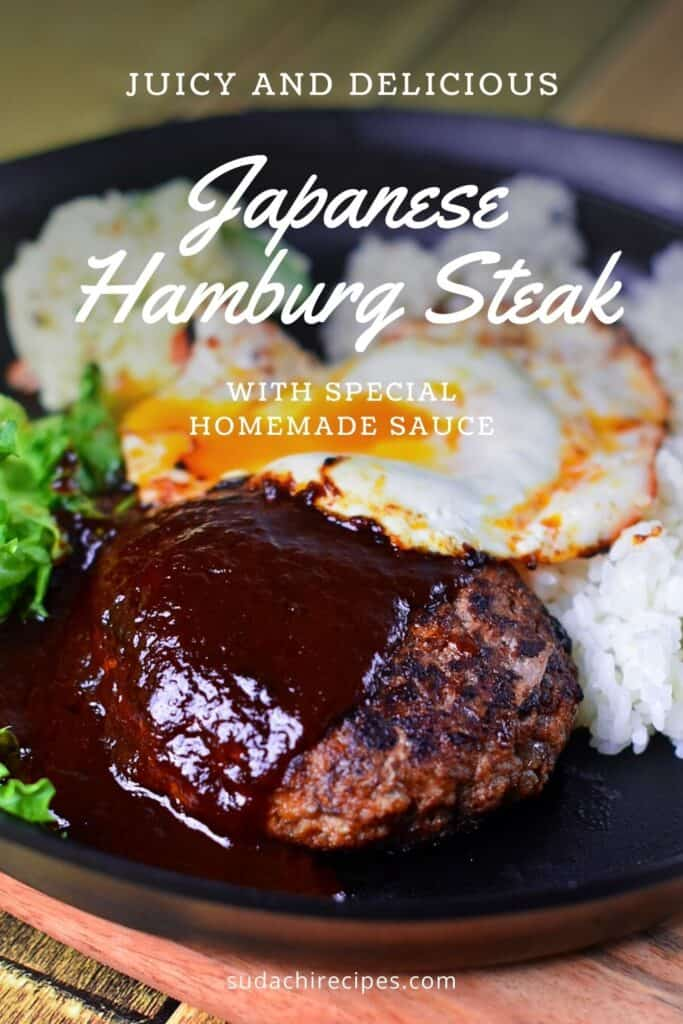 Hamburg steak on a black plate with rice, salad and a fried egg