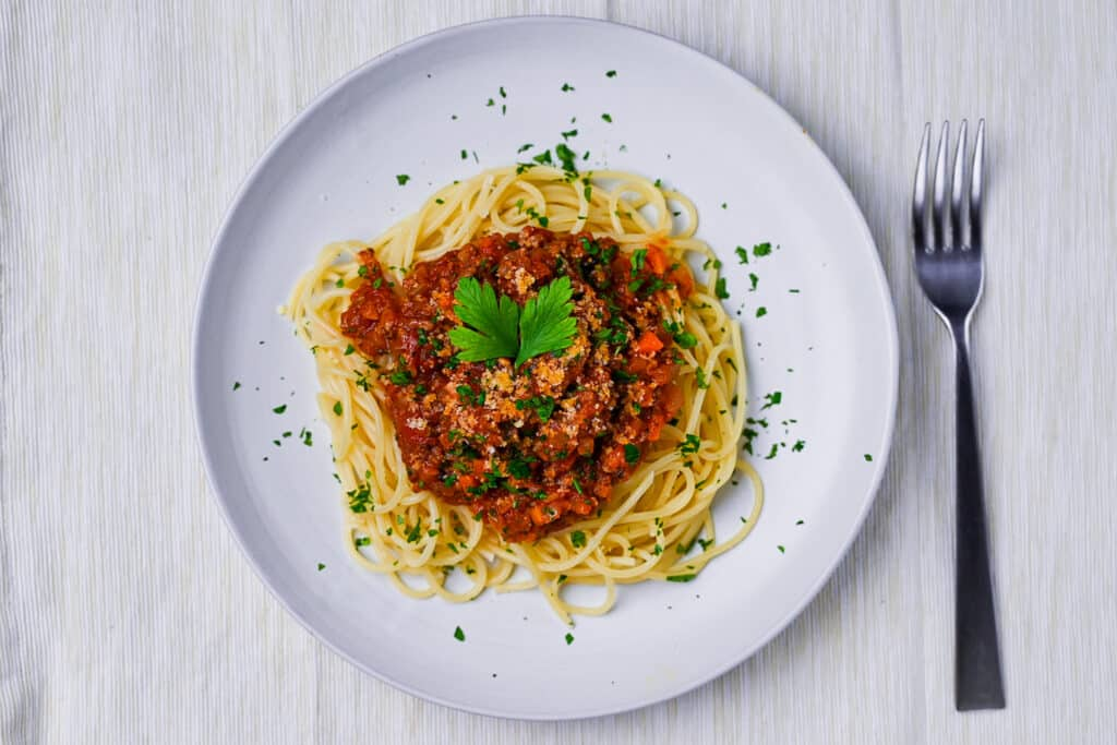 Spaghetti meat sauce served on a white plate and sprinkled with Italian parsley with fork