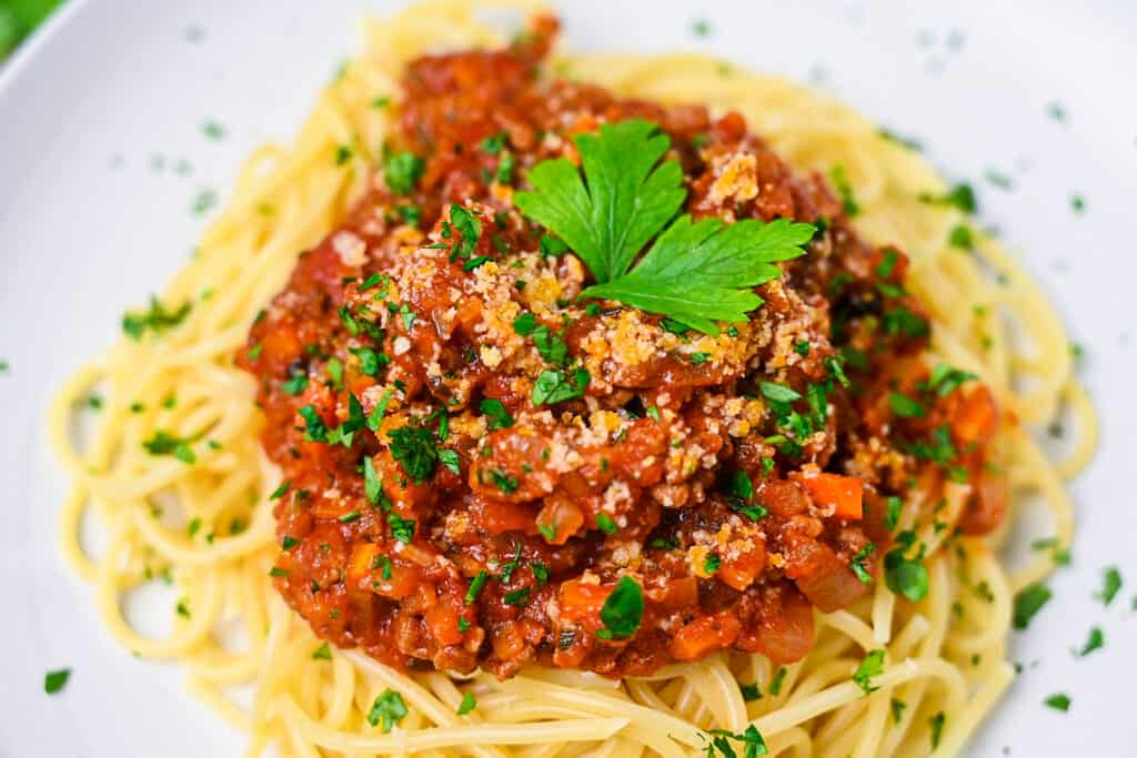 Spaghetti meat sauce served on a white plate and sprinkled with Italian parsley close up