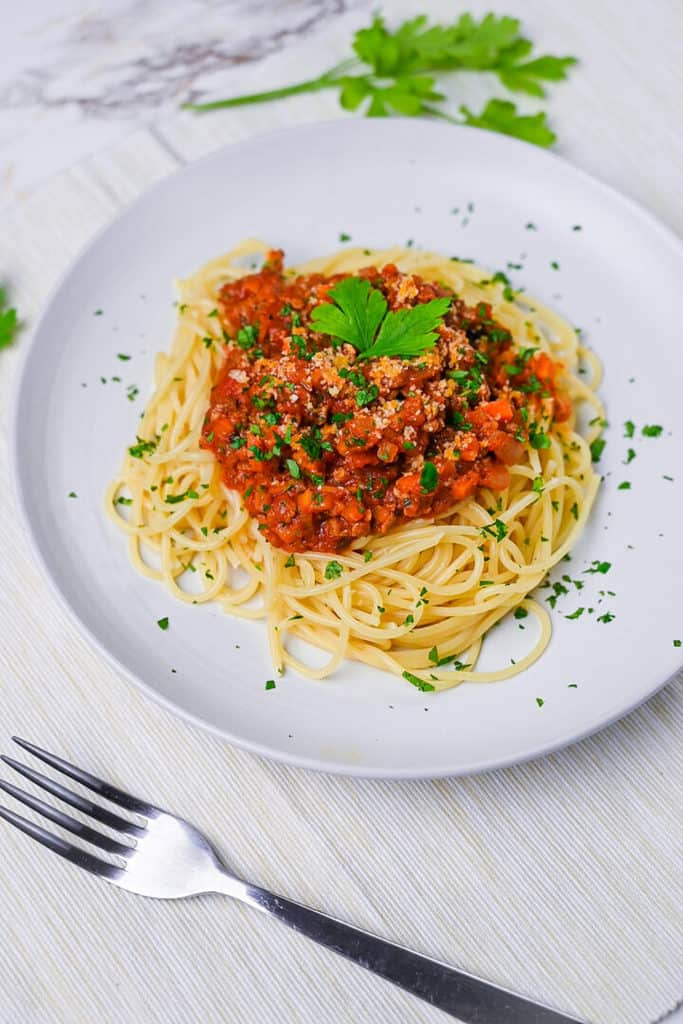 Spaghetti meat sauce served on a white plate and sprinkled with Italian parsley side view
