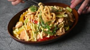 yaki udon served in a wooden bowl and being eaten with black chopsticks