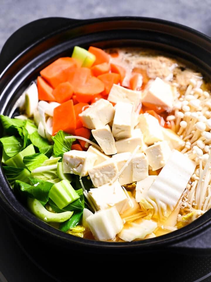 CHanko nabe with pak choi, carrots, tofu, enoki mushrooms, hakusai and chicken meatballs