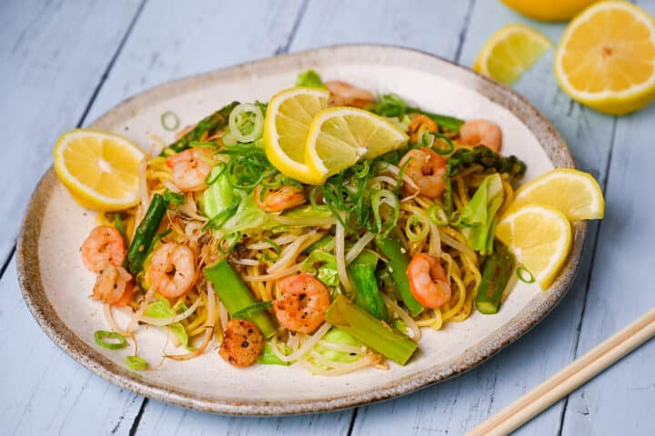 Shio Lemon yakisoba with shrimp and asparagus on a blue wood effect surface
