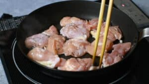 adding chicken to the pan