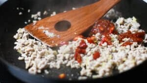 add tobanjan and red chilis to the cooked mince