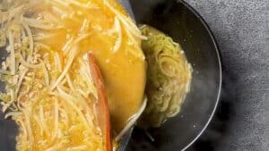 pouring broth over the noodles in a black serving bowl