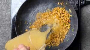 pouring broth into the pan