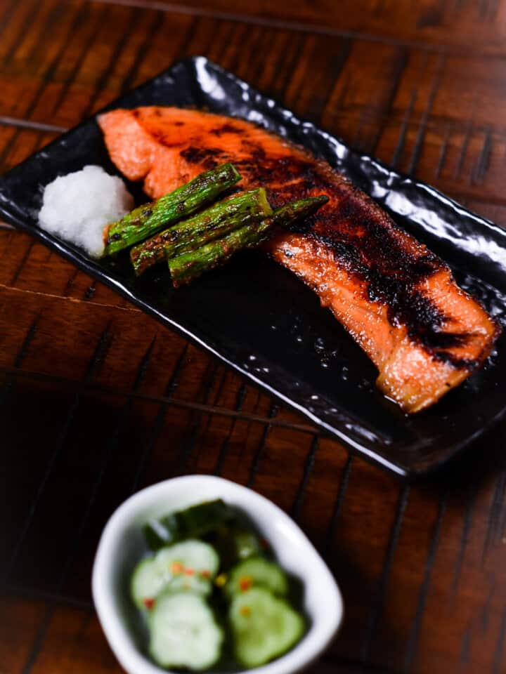 Miso salmon with asparagus served on a black plate