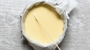 piercing air bubbles at the top of the cheesecake with a bamboo skewer