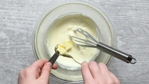 adding room temperature butter to the smooth cheesecake mixture