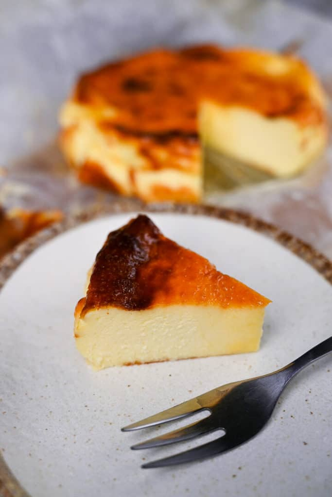 a slice of basque cheesecake on a cream colored plate with silver fork