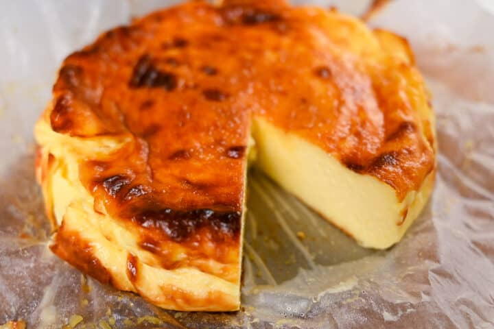 large basque cheesecake with slice missing