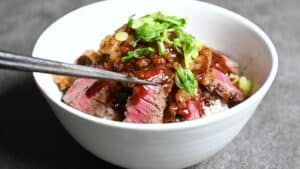Chaliapin steak don served in a white bowl, black chopsticks lifting one piece of steak