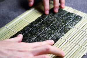 laying out the nori onto the bamboo mat