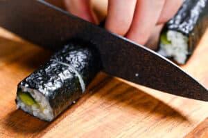 cutting kappa maki on a wooden chopping board