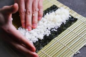 spreading sushi rice on nori