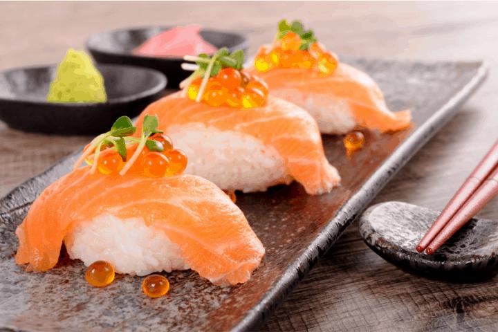 salmon nigiri sushi served on a grey plate with red chopsticks