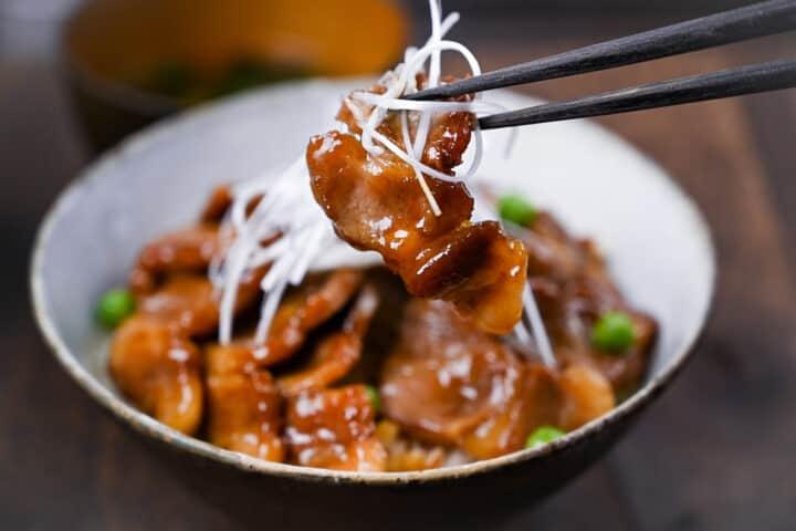 Butadon pork piece lifted by black chopsticks