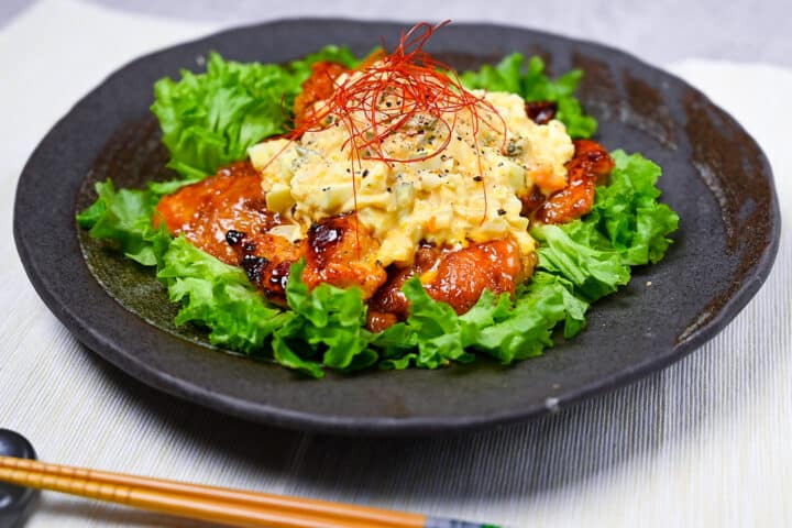 Japanese chicken nanban served on a bed of frilly lettuce on a black plate side view