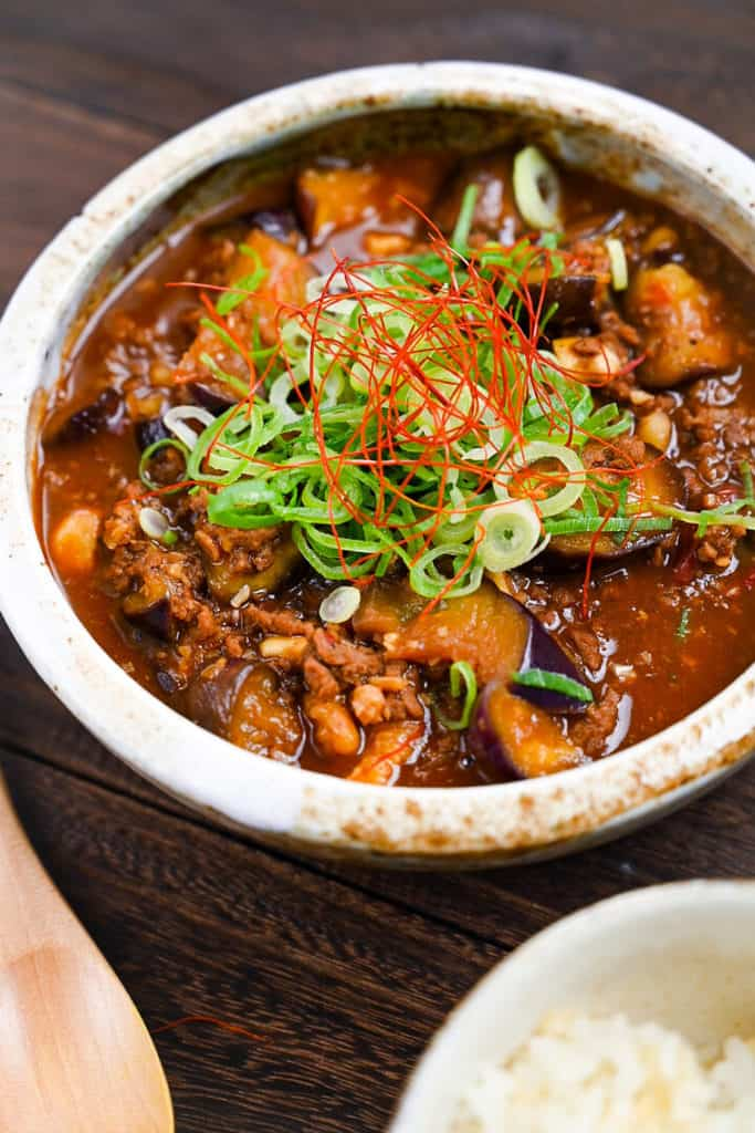 Mabo Nasu in a rustic bowl with rice, wooden spoon and scattered red chili peppers