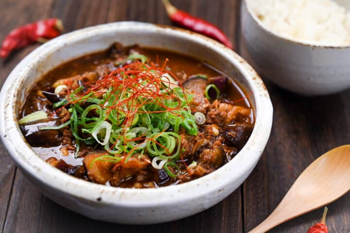 Mabo Nasu in a rustic bowl with rice, wooden spoon and scattered red chili peppers side view