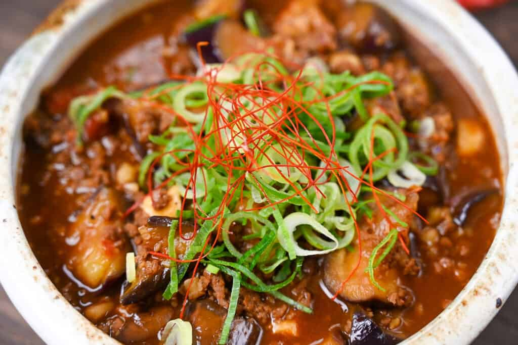 Mabo Nasu in a rustic bowl with rice, wooden spoon and scattered red chili peppers close up
