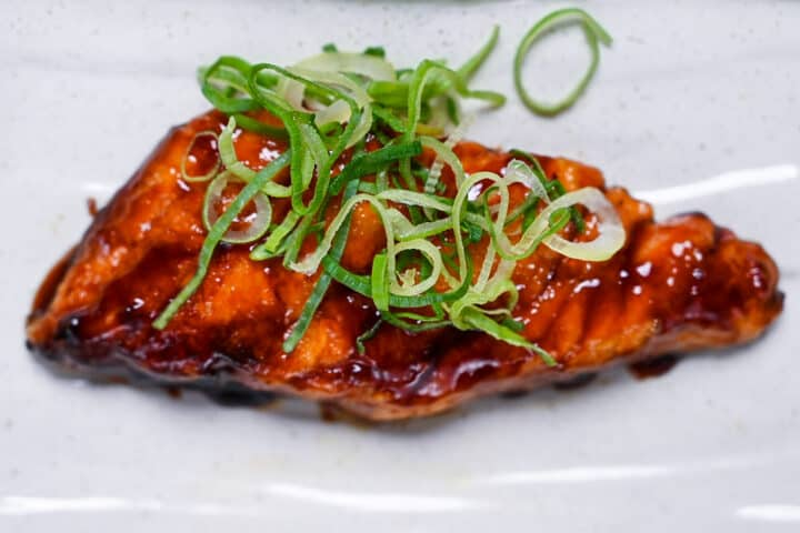 Teriyaki salmon served on a white fish plate garnished with spring onion top down view