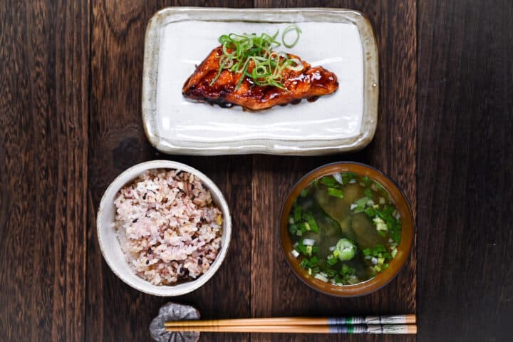Teriyaki salmon served on a white fish plate garnished with spring onion served with multigrain rice and miso soup top down view