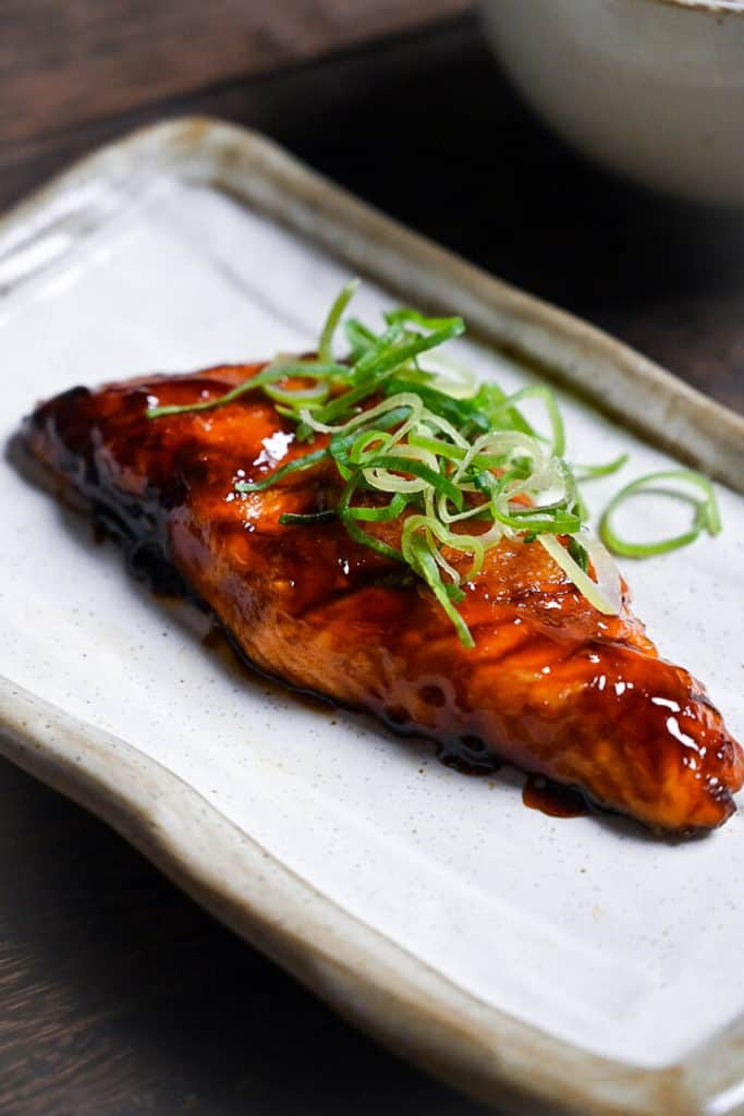 Teriyaki salmon served on a white fish plate garnished with spring onion