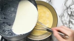 adding hot milk and cream to the egg mixture