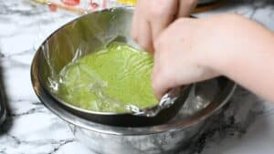 Placing plastic wrap over the surface of the matcha ice cream mixture