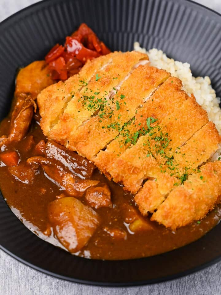 Chicken katsu curry with rice and pickles on a black plate