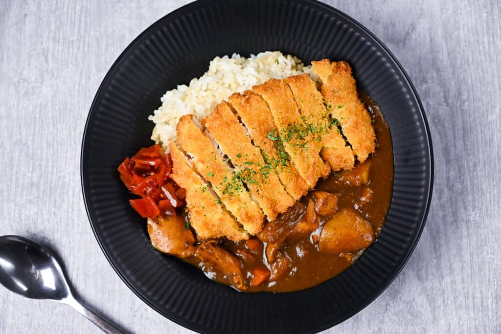 Chicken katsu curry with rice and pickles on a black plate top down