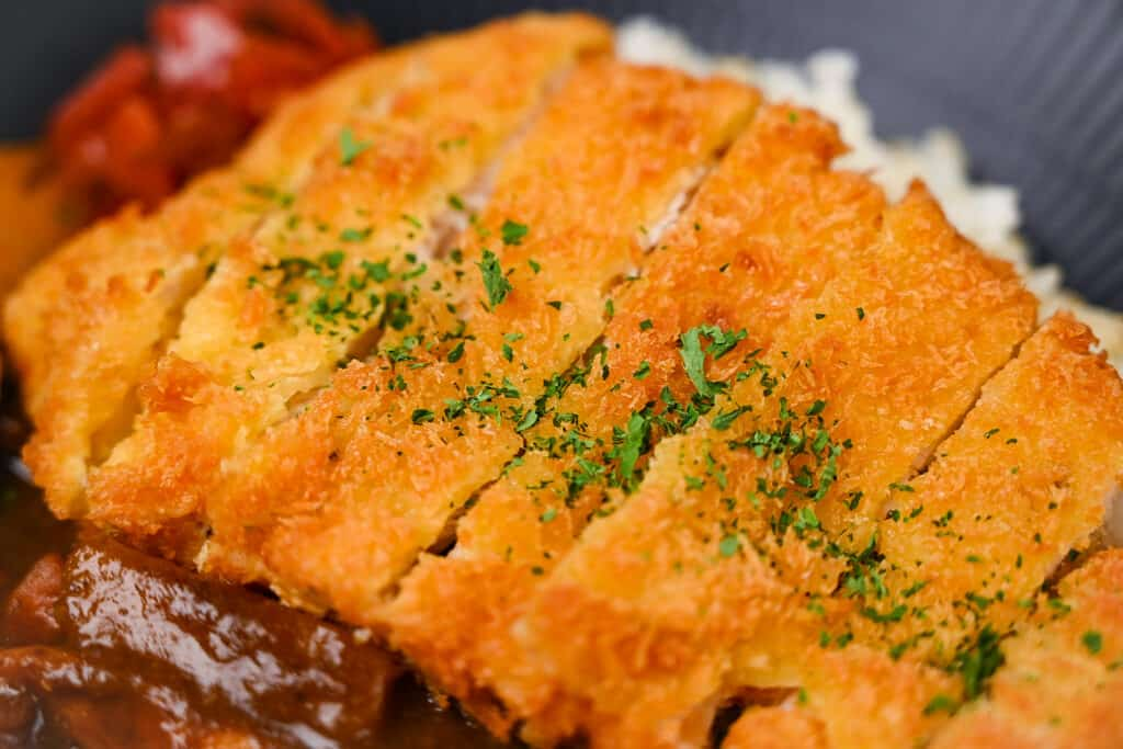 Chicken katsu curry with rice and pickles on a black plate close up
