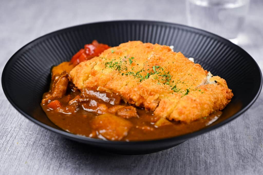 Chicken katsu curry with rice and pickles on a black plate side view