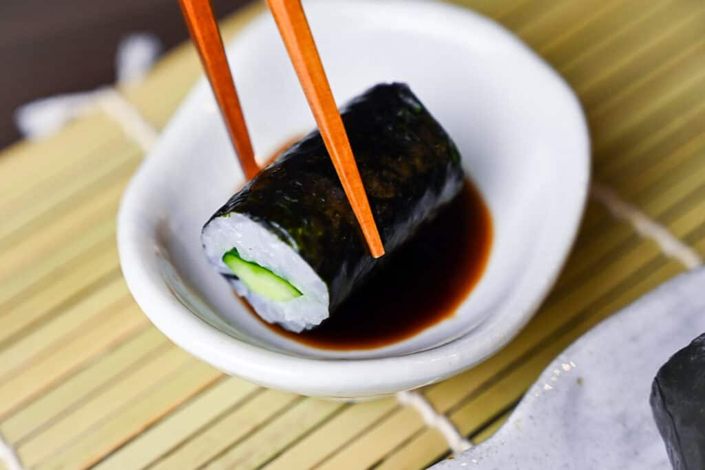 One kappa maki roll dipped in soy sauce
