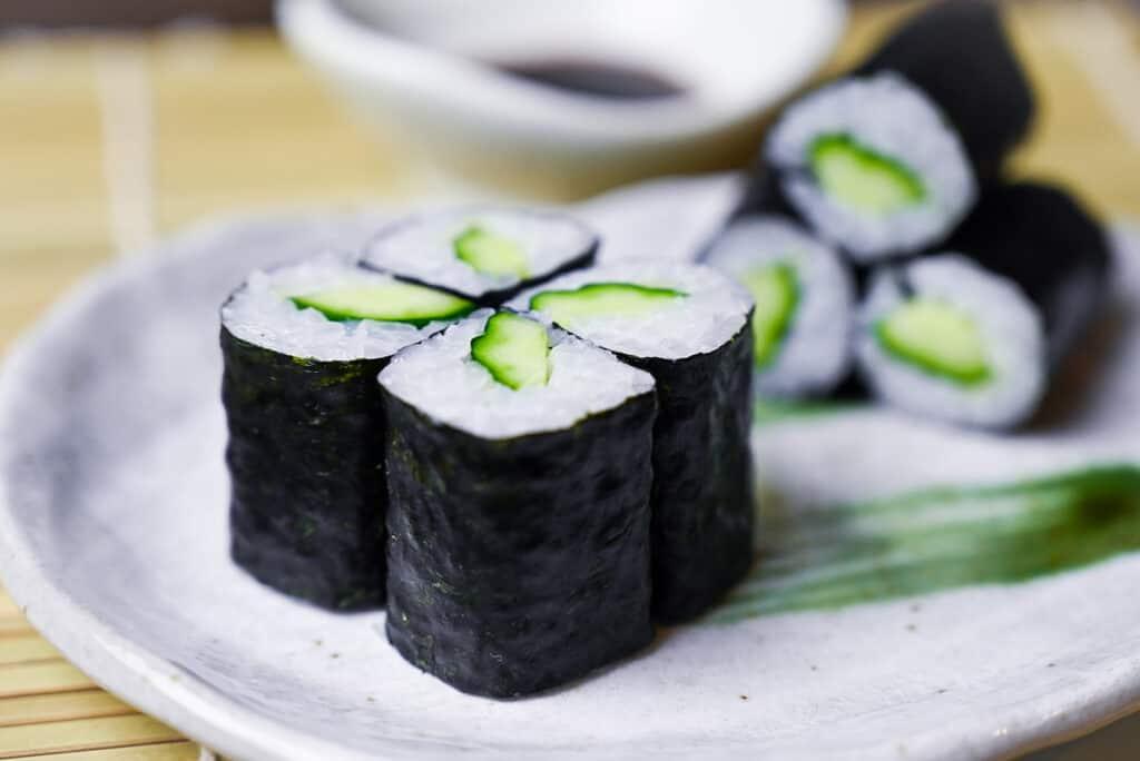 Four kappa maki sushi rolls on a plate side view