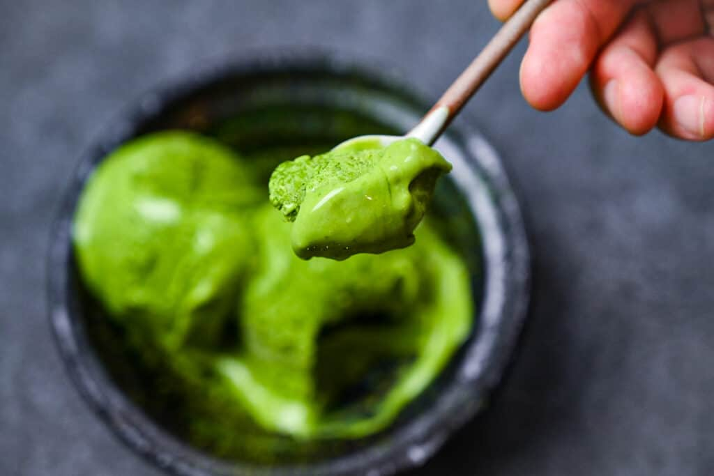 scoop of match green tea on a ceramic spoon